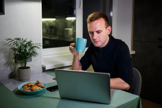 Ritratto di un giovane sorridente che lavora su un laptop da casa e beve caffè da una tazza ed è soddisfatto del suo lavoro. appartamento moderno e accogliente. lavoro a casa, concetto di business online