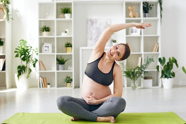 Ritratto di giovane donna incinta sorridente in abito sportivo seduto con le gambe incrociate e piegandosi da parte con il braccio alzato mentre si pratica lo yoga a casa