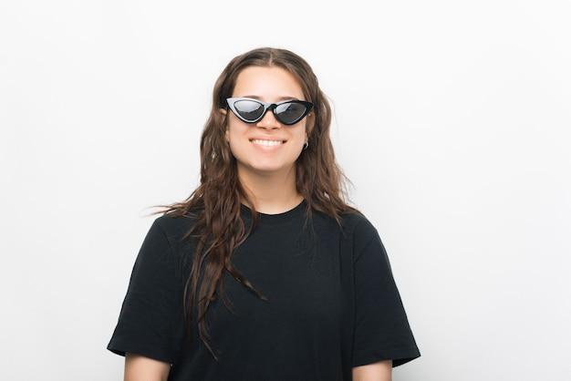Ritratto di giovane donna alla moda sorridente in maglietta nera e occhiali da sole
