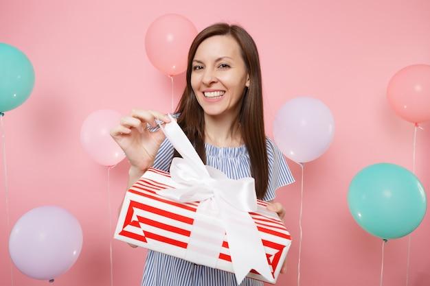 Ritratto di giovane donna sorridente in abito blu che slega l'arco sulla scatola rossa con regalo presente su sfondo rosa pastello con mongolfiere colorate. festa di compleanno, concetto di emozioni sincere della gente.