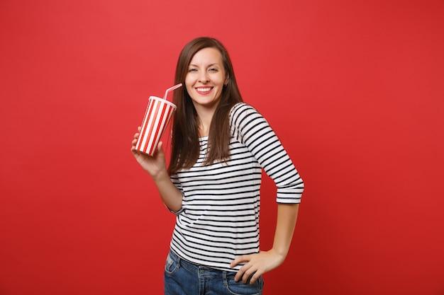Ritratto di giovane donna sorridente in abiti casual a righe che tengono tazza di plastica di cola o soda isolata su sfondo rosso brillante persone sincere emozioni, concetto di stile di vita. mock up copia spazio.
