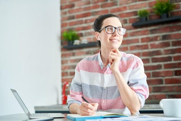Il ritratto della giovane donna sorridente che fantastica il lavoro mentre studia a casa, copia lo spazio