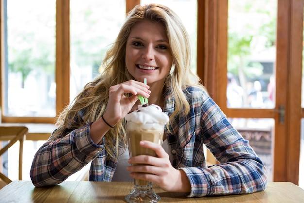 Ritratto di sorridente giovane donna che beve frappè con paglia nella caffetteria