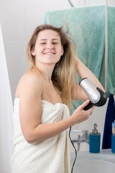 Ritratto di giovane donna sorridente che asciuga i capelli lunghi in bagno