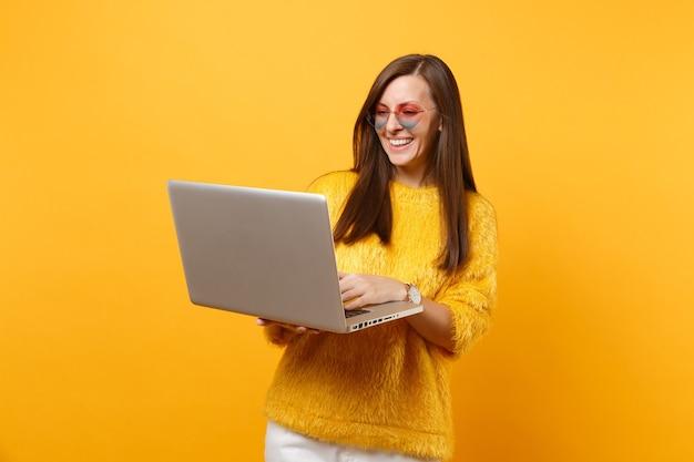 Ritratto di giovane donna sorridente in maglione di pelliccia e occhiali a cuore che lavorano su computer pc portatile isolato su sfondo giallo brillante. persone sincere emozioni, concetto di stile di vita. zona pubblicità.