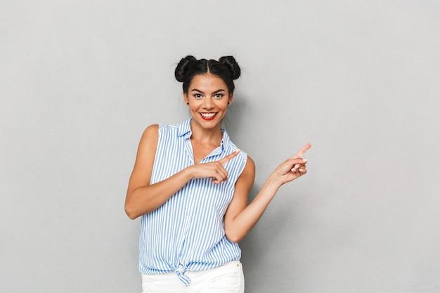 Ritratto di una giovane donna sorridente isolata, indicando