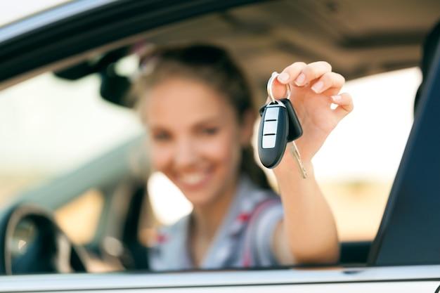 Ritratto di giovane donna sorridente che guarda fuori dal finestrino della sua auto che mostra la chiave dell'auto