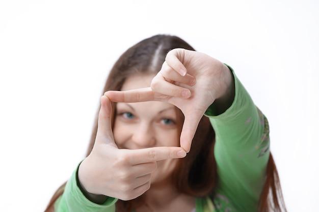 Ritratto di una giovane donna sorridente che fa una cornice dalle sue mani