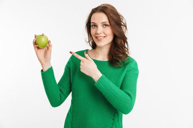 Ritratto di una giovane donna sorridente che punta il dito alla mela