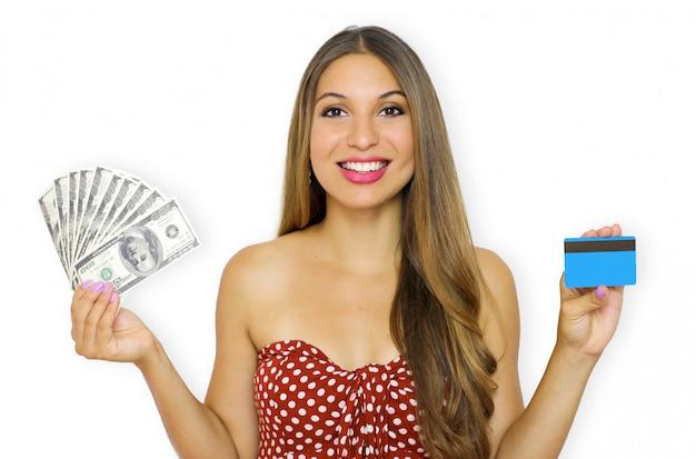Ritratto di una giovane donna sorridente che mostra mazzo di banconote di denaro e tenendo la carta di credito in plastica
