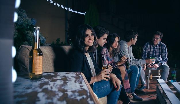 Ritratto di giovane donna sorridente che si siede e tiene una birra mentre i suoi amici parlano in una festa all'aperto. concetto di amicizia e celebrazioni.