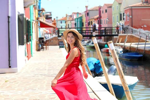Ritratto di una giovane donna sorridente in cappello estivo corre nel villaggio di burano con case colorate, venezia, italia