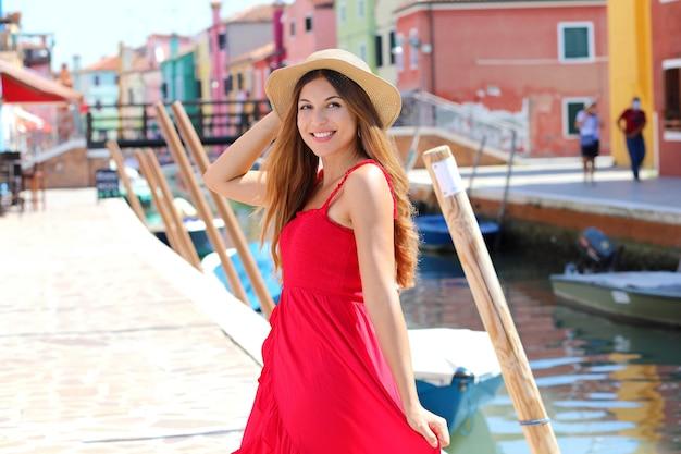 Ritratto di una giovane donna sorridente in cappello estivo passeggiate nel villaggio di burano con case colorate, venezia, italia