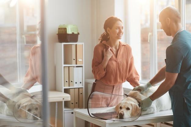 Ritratto di una giovane donna sorridente che parla con un veterinario che esamina un cane presso una clinica veterinaria, scena illuminata dalla luce del sole, spazio copia