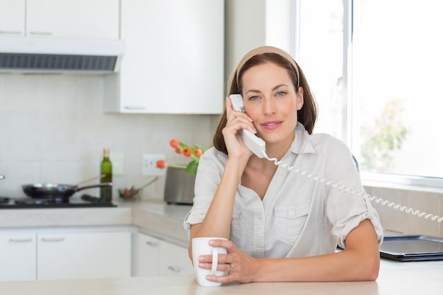 Ritratto di una giovane donna sorridente con la tazza di caffè che utilizza il telefono della linea terrestre nella cucina a casa