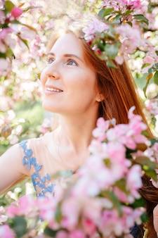 Ritratto di una giovane donna sorridente con i capelli rossi e la pelle pulita in un meleto in fiore messa a fuoco selettiva immagine luce solare colorata primo piano verticale