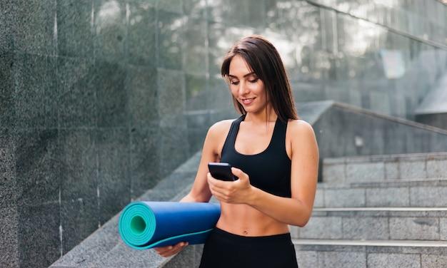 Ritratto di donna in forma smilling con un corpo perfetto che tiene in mano il materassino yoga piegato e utilizza lo smartphone