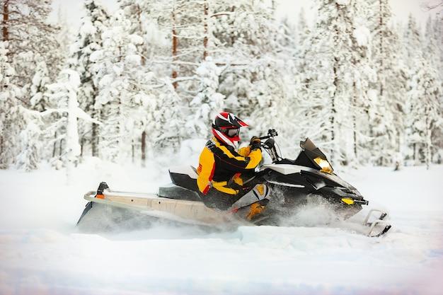 Ritratto di un pilota di motoslitta in attrezzatura con casco in sella a una superficie di neve all'aperto