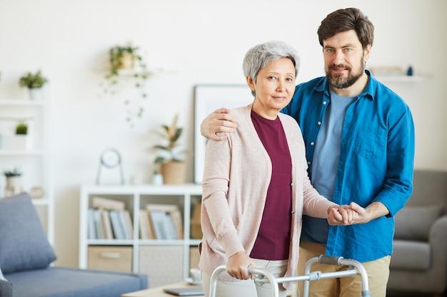 Ritratto del figlio che abbraccia la sua madre senior con il camminatore mentre stanno nella stanza domestica e che guarda l'obbiettivo