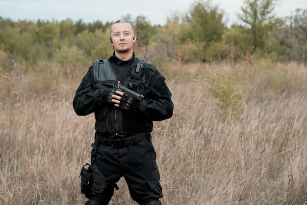 Ritratto del soldato delle forze speciali in uniforme nera con una pistola