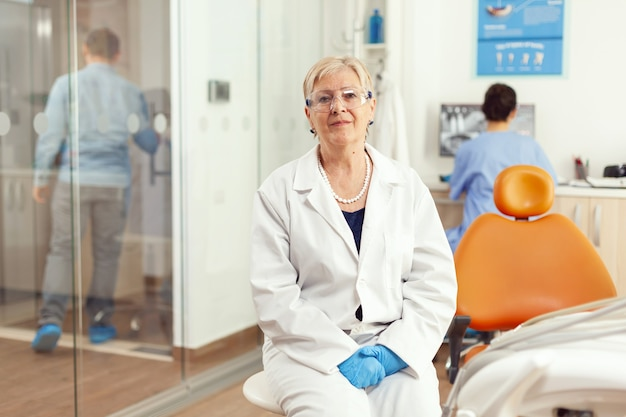 Ritratto di medico specialista che lavora nella stanza dell'ufficio stomatologico che si prepara per la chirurgia odontoiatrica durante la consultazione ortodontica del paziente malato