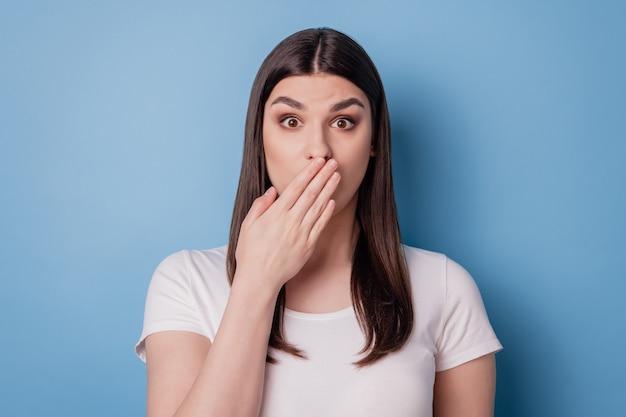 Ritratto di una signora pazza che fissa senza parole la bocca della copertura della palma che guarda la telecamera su sfondo blu