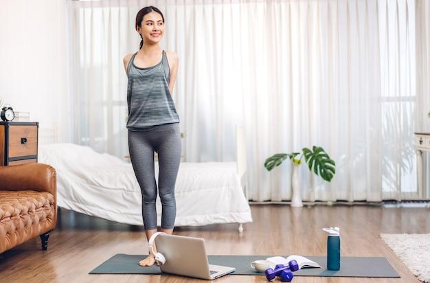 Ritratto sport bellezza asiatica corpo sottile donna in abbigliamento sportivo rilassarsi e praticare yoga e fare esercizio di fitness con il computer portatile in camera da letto a casa. concetto di dieta. fitness e stile di vita sano