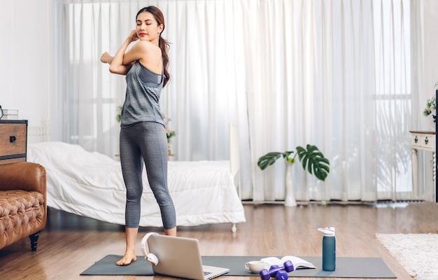 Ritratto di donna asiatica di sport in abiti sportivi rilassarsi e praticare lo yoga e fare esercizio di fitness con il computer portatile in camera da letto a casa.