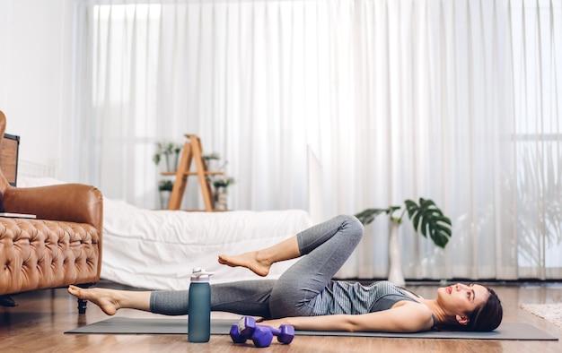 Il ritratto della donna asiatica di sport nella seduta degli abiti sportivi si rilassa e pratica lo yoga e fa esercizio di fitness in camera da letto a casa.