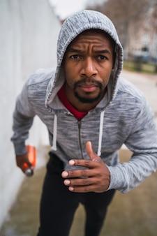 Ritratto di un uomo di sport in esecuzione su scale all'aperto. concetti di fitness, sport e stile di vita sano.