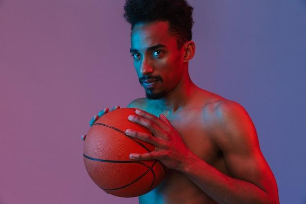 Ritratto di uomo afroamericano sportivo senza camicia in posa con pallacanestro isolato su muro viola
