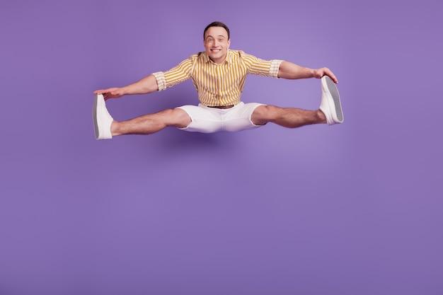 Il ritratto del ragazzo flessibile attivo sportivo salta le mani tocca le gambe su sfondo viola
