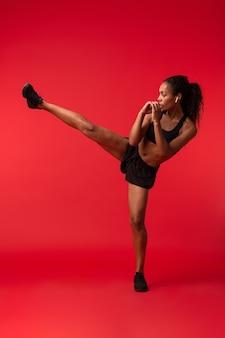 Ritratto di donna afroamericana sportiva in abiti sportivi neri che fa calci, isolato sopra la parete rossa
