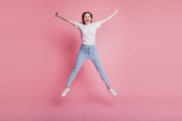 Il ritratto della ragazza funky infantile e sportiva che salta nell'aria indossa un abito casual in denim sulla parete rosa