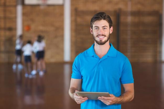 Ritratto dell'insegnante di sport che per mezzo della compressa digitale