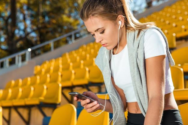 Ritratto di una donna sportiva utilizza lo smartphone sullo stadio all'aperto