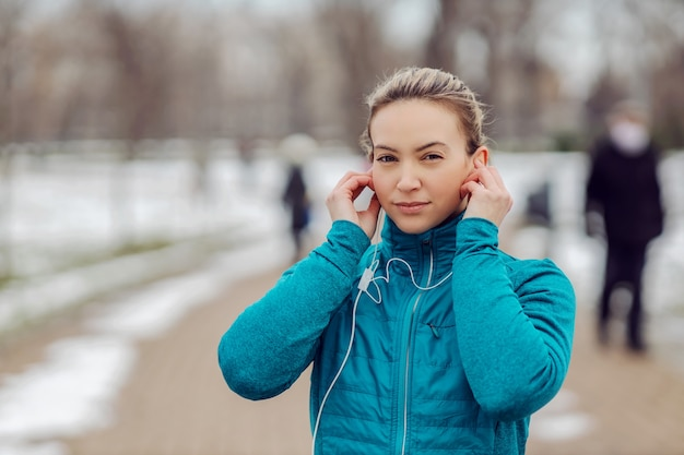 Ritratto di sportiva in abito caldo in piedi nel parco pubblico in caso di neve e mettendo gli auricolari.