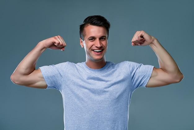 Ritratto di ragazzo sportivo, attraente, potente, virile, duro e sexy in t-shirt con le braccia alzate, con muscoli di sollievo sulle mani, isolato su sfondo grigio