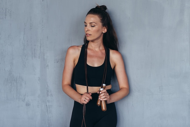 Ritratto di una ragazza sportiva con una corda per saltare in piedi contro il muro.