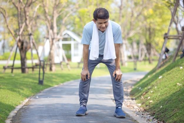 Ritratto di sportivo maschio maturo sano in felpa con cappuccio e scarpe da corsa che esercitano all'aperto, praticando affondi laterali. uomo barbuto anziano in abiti sportivi in fase di riscaldamento prima della corsa mattutina nel parco