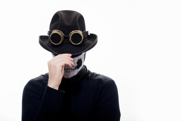 Ritratto di un uomo steampunk con lo scheletro di cappello e maschera isolato