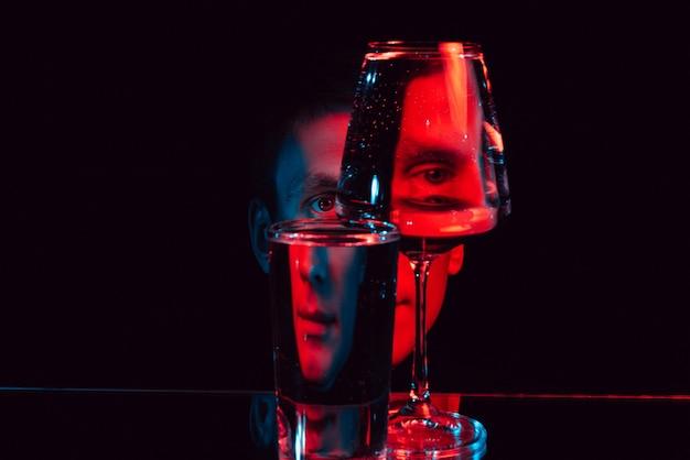 Ritratto di uno strano uomo che guarda attraverso bicchieri di vetro d'acqua con riflessi e distorsioni con luce al neon blu rossa