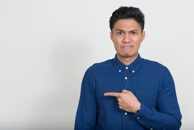 Ritratto dell'uomo d'affari asiatico sollecitato che sembra disgustato
