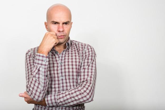 Ritratto di uomo d'affari calvo stressato pensando e guardando verso il basso