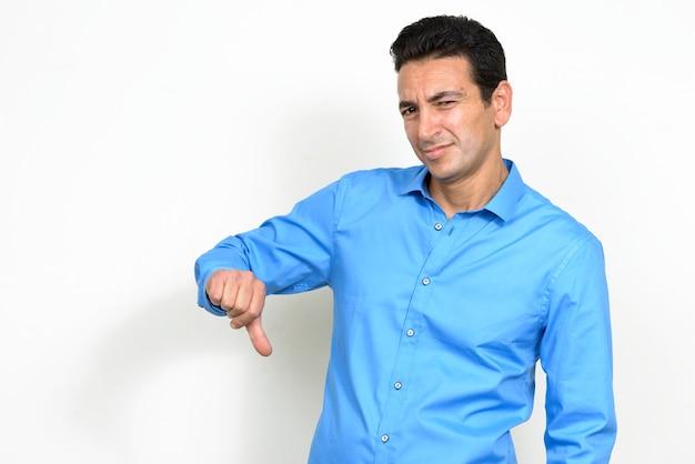 Ritratto dell'uomo d'affari maturo sollecitato che sembra disgustato e che dà i pollici giù