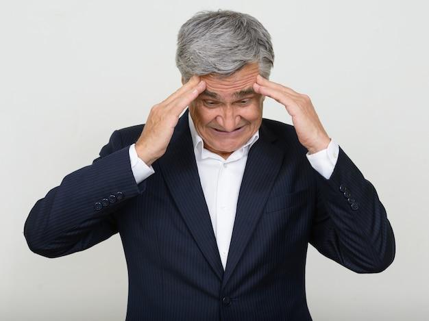 Ritratto dell'uomo d'affari maggiore sollecitato in vestito che ha mal di testa