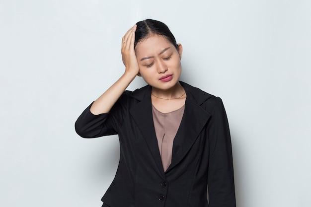 Ritratto di donna d'affari asiatica malata stressata con mal di testa?