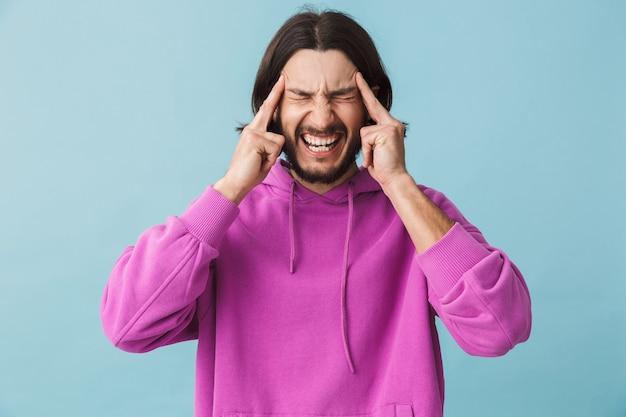 Ritratto di un giovane uomo bruna barbuto stressato che indossa una felpa con cappuccio in piedi isolato su un muro blu, che soffre di mal di testa