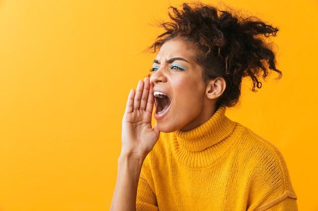 Ritratto di stressante donna afro-americana con acconciatura afro urlando o chiamando stando in piedi, isolato