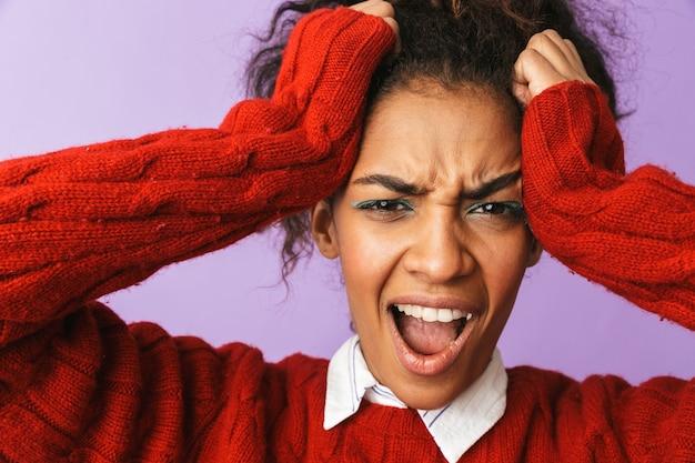Ritratto di stressante donna afro-americana con acconciatura afro urlando e afferrando la testa, isolata